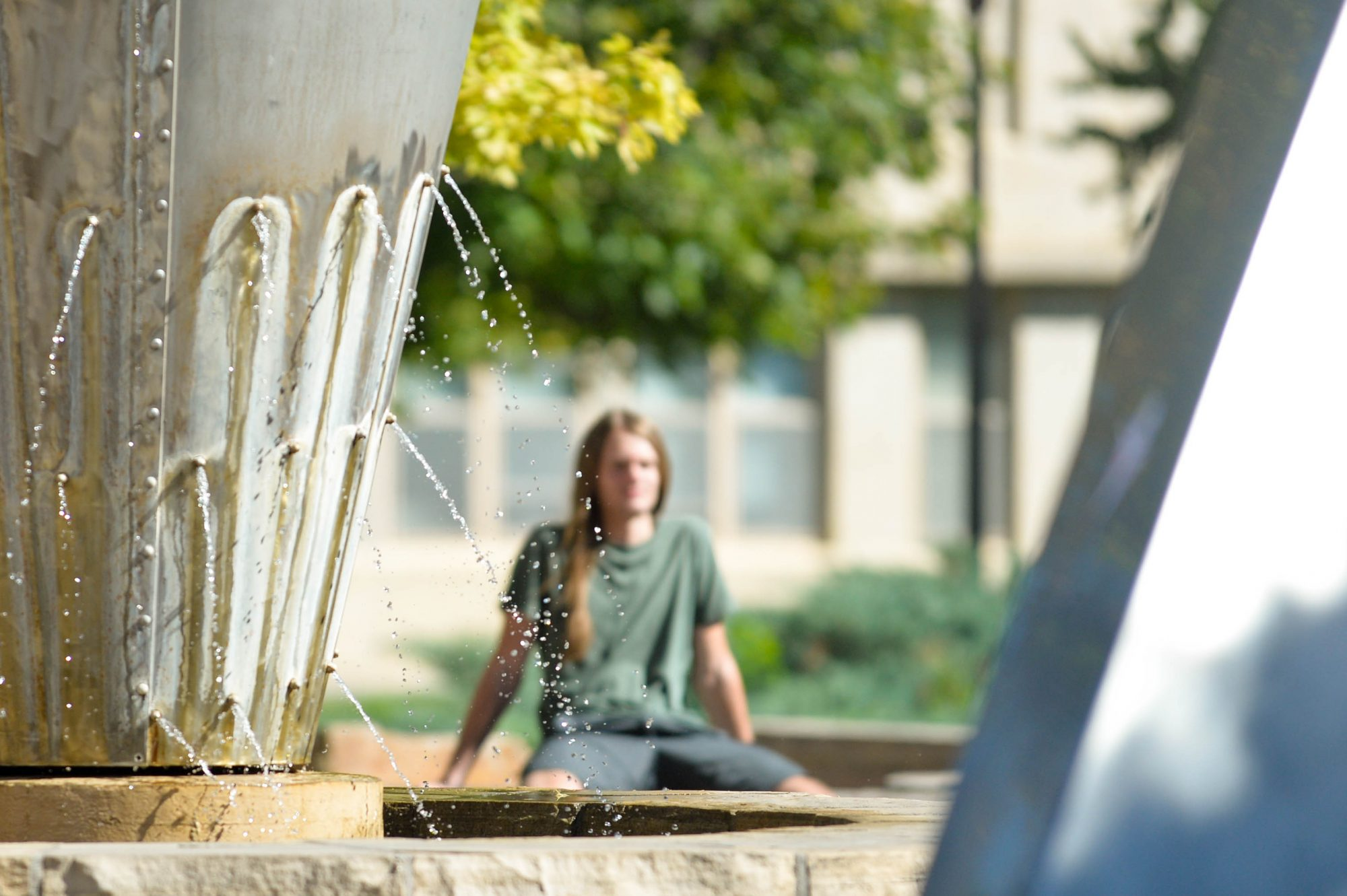A CSU student relaxes on campus by an outdoor fountain